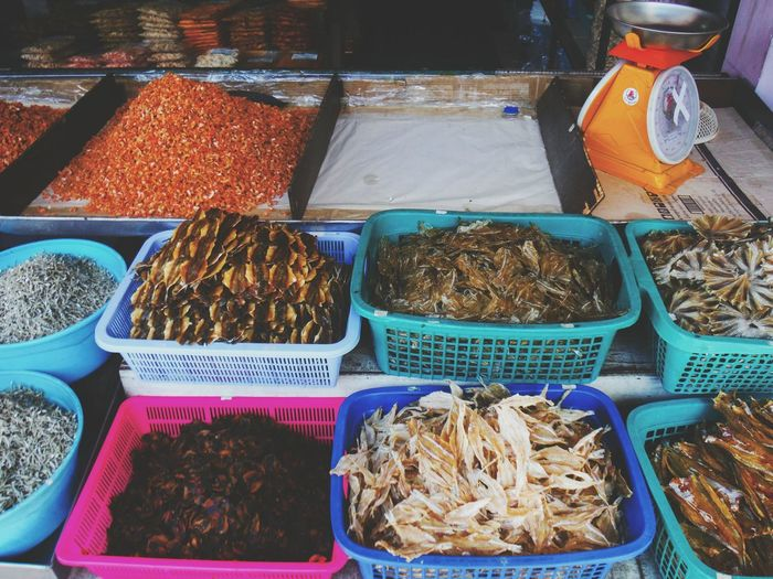 High angle view of dried fish in container for sale at market stall