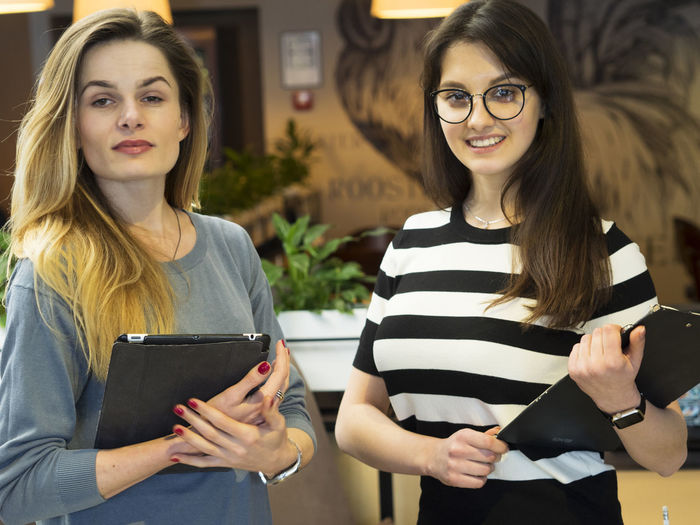 Portrait Of Confident Young Women With Digital Tablet And Clipboard Standing In Restaurant