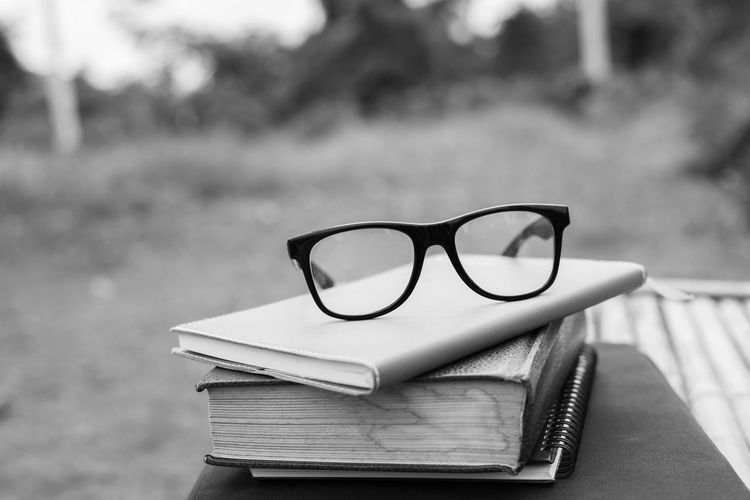 Close-up of eyeglasses on books outdoors