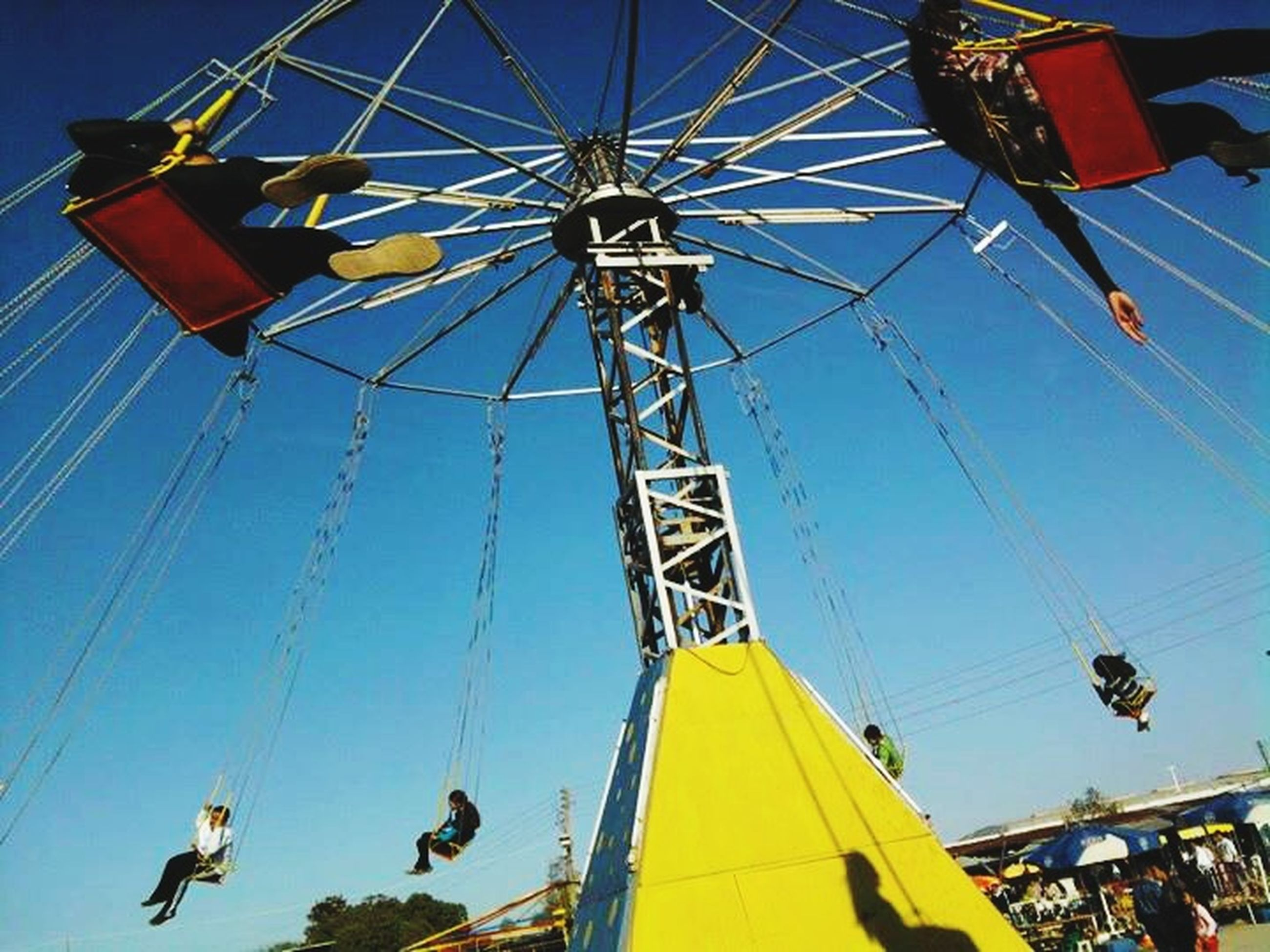 low angle view, amusement park ride, amusement park, blue, sky, multi colored, fun, clear sky, arts culture and entertainment, hanging, day, power line, flag, outdoors, enjoyment, ferris wheel, chain swing ride, no people, cable, leisure activity