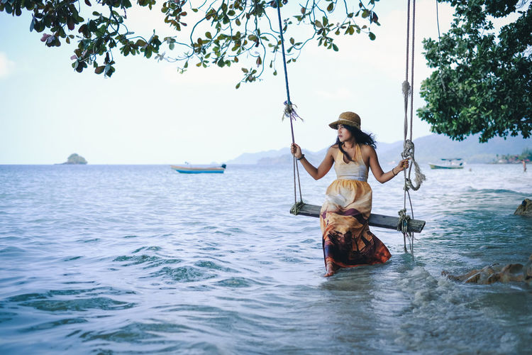 Travel Background Place ASIA Asian  Thailand Nature Stone Vacations Coast Holiday Sky And Clouds Relaxing Lifestyle Summer Looking Visiting Young Women Water Sea Women Full Length Beauty Portrait Tree Beautiful People Sky Boat Calm Shore Rope Swing Swing Rowing Rippled