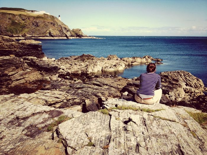 Girl sitting on rocks overlooking bay Isle Of Man Maughold lighthouse