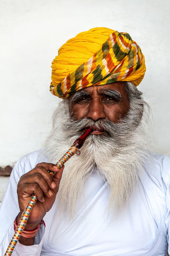 This is, I believe, the most photographed man in Jodhpur, Rajasthan, India. He sits inside one of the first courtyards of the majestic Mehrangarh Fort and for what I understand his job is to just sit there, smoke the water pipe and look fabulous so that tourists can take his picture. The thing is, he does a fantastic job of looking fabulous and so, like everyone else, I had a go at taking his portrait! :-) Mehrangarh Smoking Tourist Attraction  Water Pipe Beard Fabulous Front View Gaze Looking At Camera Model Narghile Older Man One Man Only One Person Portrait Tourist Destination Traditional Clothing Travel Portraits Turban