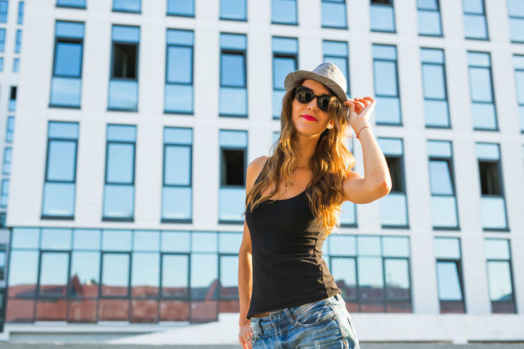 Woman wearing hat standing against built structure
