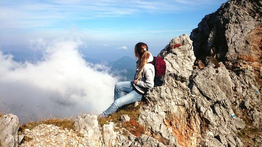 Female Hiker Sitting On Rocky Mountain Against Sky