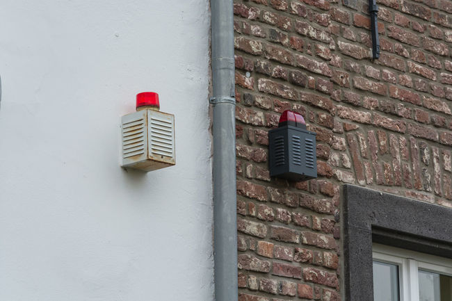 Two alarm systems with warning lights on a house wall Flashing Lamp Signal Light Architecture Brick Wall Building Exterior Built Structure Close-up Day Flashing Lights No People Outdoors Red Wall - Building Feature Warning Light