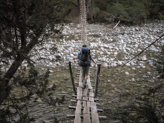 Rear View Of Man Walking On Footbridge Over Stream