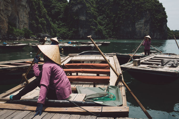 Side View Of Woman Wearing Asian Style Conical Hat While Sitting On Rowboat At Halong Bay