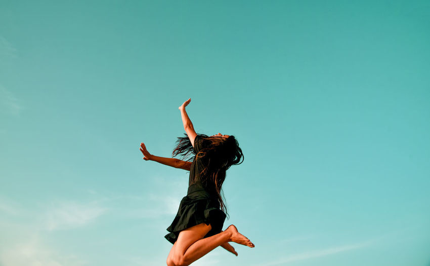 Woman jumping with arms raised against sky