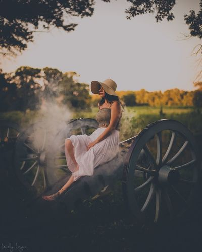 Full length of young woman sitting on cart at farm against sky