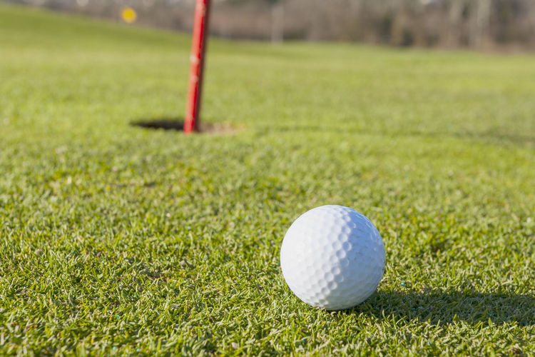 Close-up of a golf ball with the hole Golf Sport Ball Golf Ball Grass Golf Course Activity Green - Golf Course Leisure Activity Green Color Plant Focus On Foreground No People Day Close-up Nature White Color Golf Flag Outdoors Flag At The Edge Of