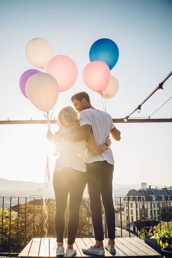 Rear View Of Couple Standing With Balloons Against Sky
