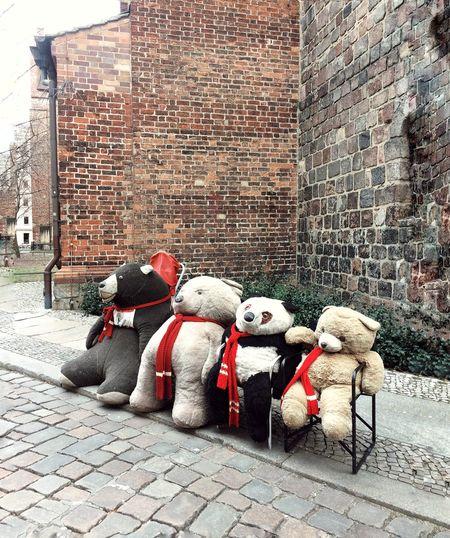 Toys on street against brick wall
