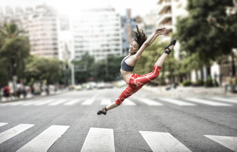 Full length of woman jumping on road