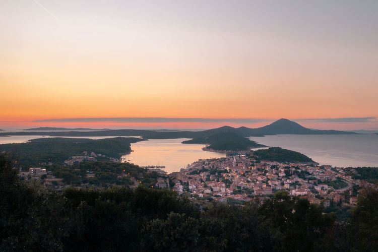 High angle view of sea and cityscape against sky during sunset