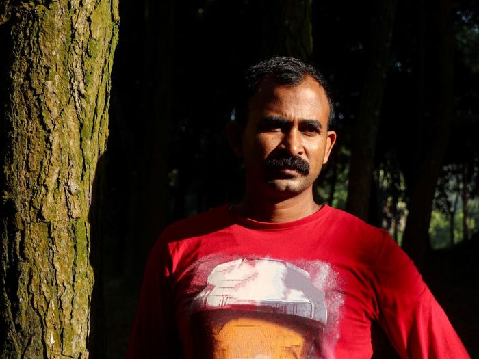Portrait of man standing by tree trunk