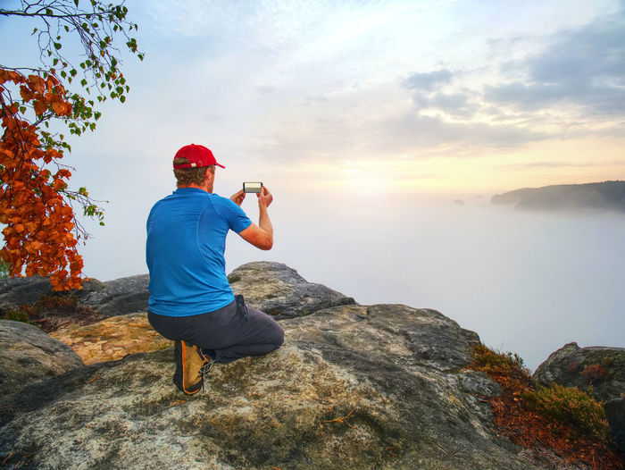 Rear view of man on rock against sky during sunset
