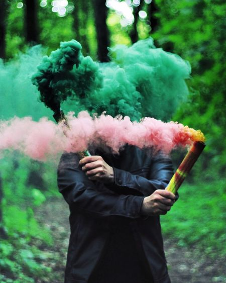 Man holding distress flares in forest