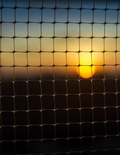 Full Frame Shot Of Metal Grate Against Sky During Sunset