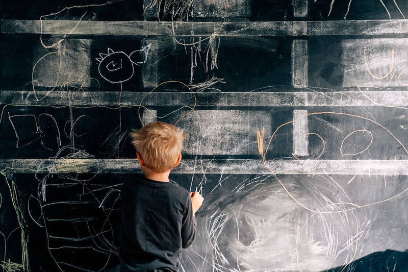 Rear view of boy writing on blackboard