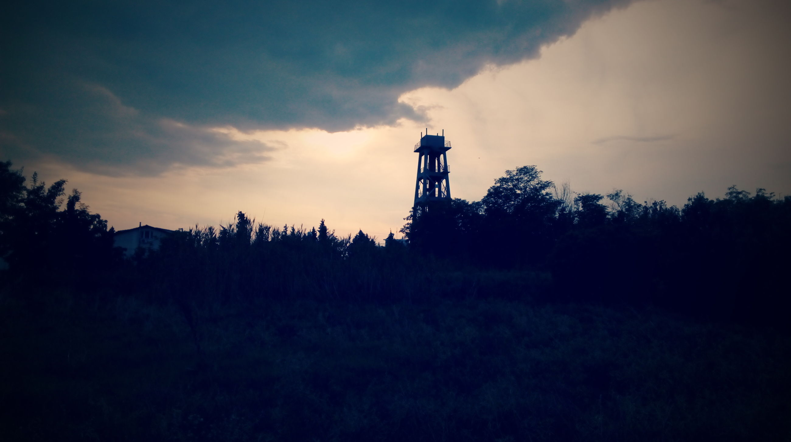 sky, lighthouse, tree, guidance, built structure, silhouette, sunset, architecture, tower, landscape, low angle view, direction, cloud - sky, nature, building exterior, tranquility, field, tranquil scene, beauty in nature, dusk