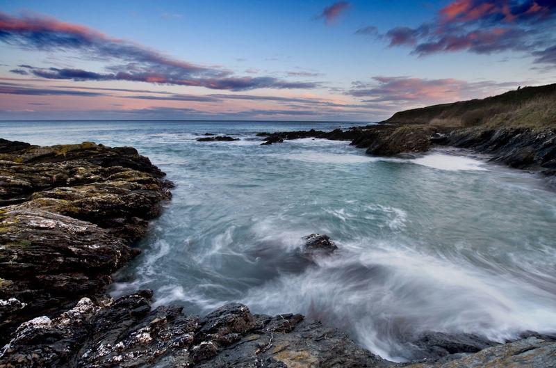 View of water splashing on rocks at sea