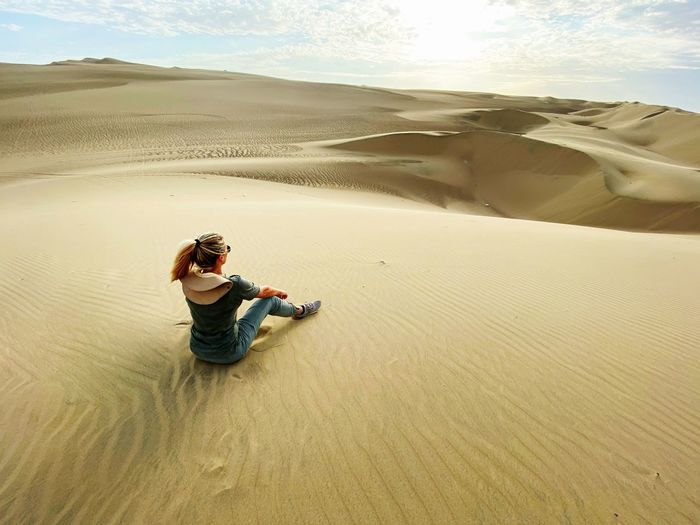 Rear view of woman sitting at desert