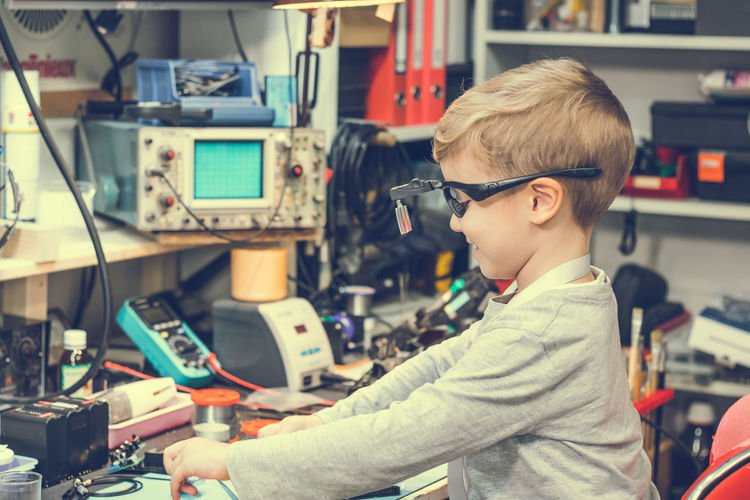 Boy repairing computer part on table at home