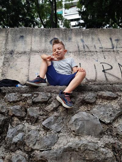 Full length of boy sitting on wall