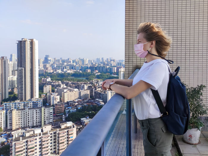 Rear view of woman looking at modern buildings in city from the roof top