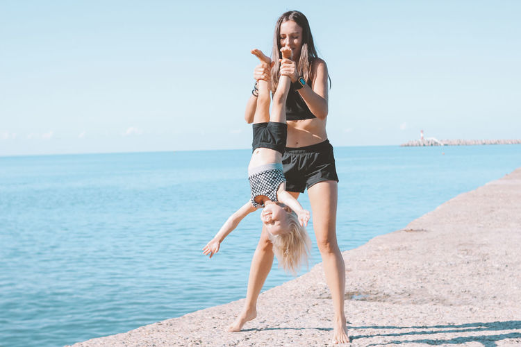 Full length of mother holding daughter upside down at beach against sky