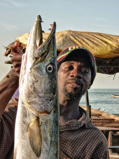 Fisherman with his catch. Africa Barracuda Big Fish Catch Fish Fisherman Gambia  People Port Portrait Sea Smiling Coast The Gambia Tourism Travel