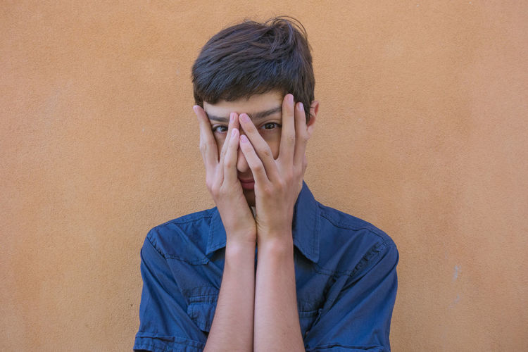 teen boy hiding face by hands Casual Clothing Headshot Hiding Lifestyles One Person Outdoors People Real People Teen Teenager Wall Young Adult