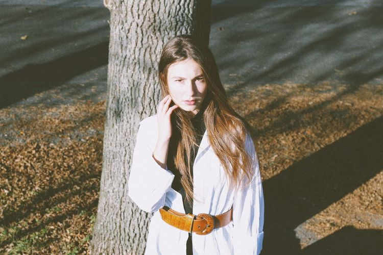 Portrait of young woman standing on tree trunk
