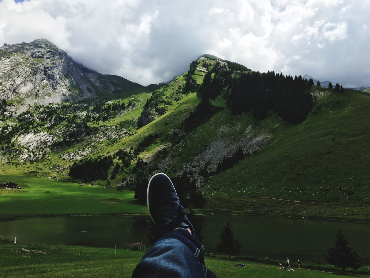 Low Section Of Man Relaxing On Field Against Mountains
