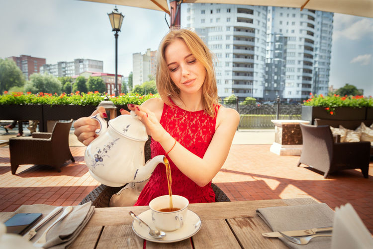 Smiling young woman with drink in cafe