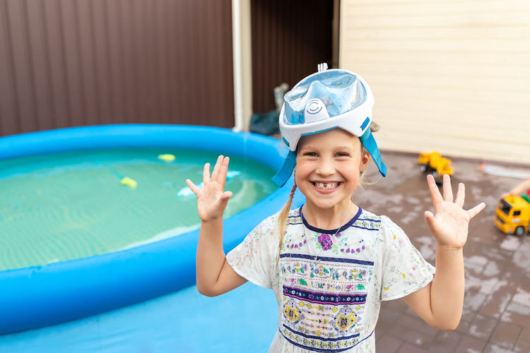Portrait of smiling girl standing by wading pool