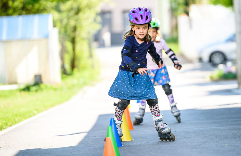 Portrait Of Girl Roller Skating Through Cones On Road