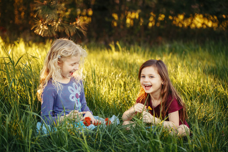 Happy children girls playing dolls in park. outdoor summer backyard activity for kids