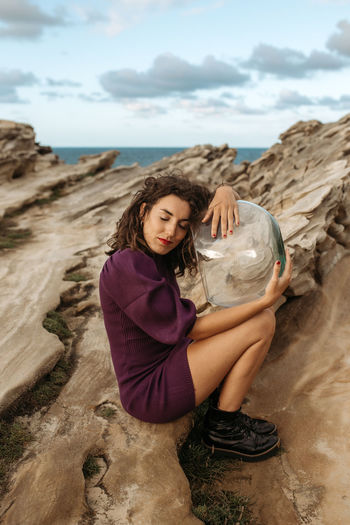 Young woman on rock at beach against sky