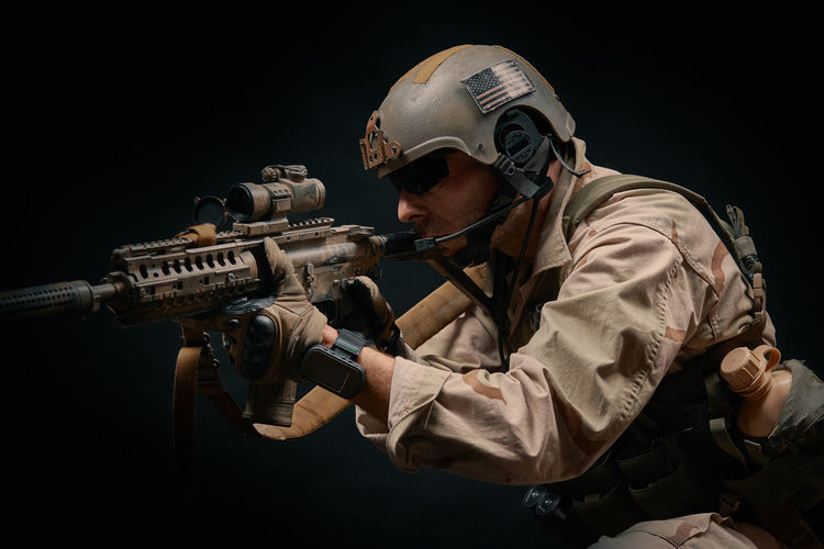 Man wearing helmet holding rifle against black background