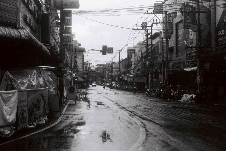 Wet street amidst buildings in city
