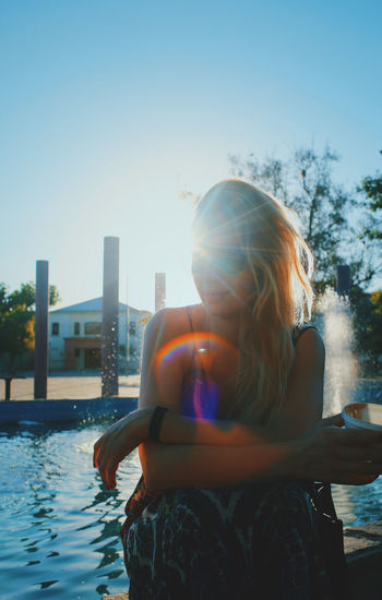 Young woman by swimming pool against clear sky