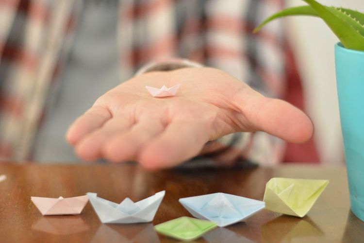 Midsection of person holding paper boat at table
