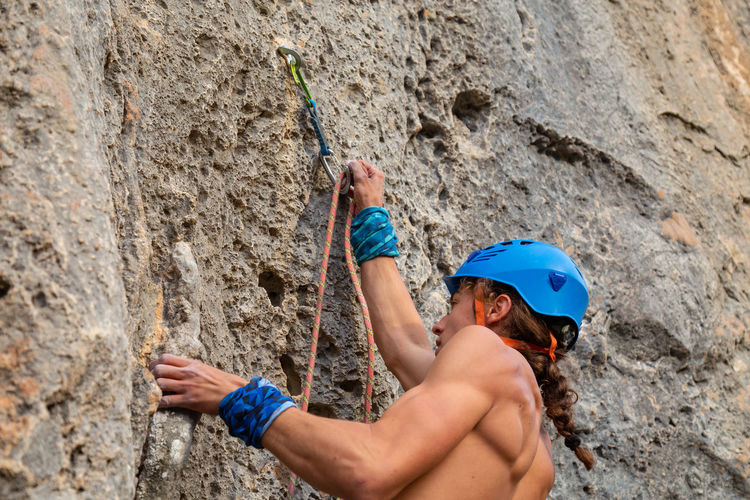 Young climber man putting the carabiner with his hand to make sure on the rock Man Climbing Climber Mountain Rock Cliff Sunny Shirtless Sport Extreme Sports Activity Height Rope Challenge Strong Adventure RISK Exercising Grip Young Adult Fearless Athlete Training Difficult Carabiner