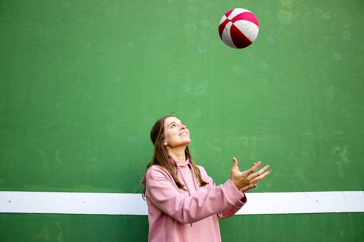 Smiling young woman playing with ball against wall