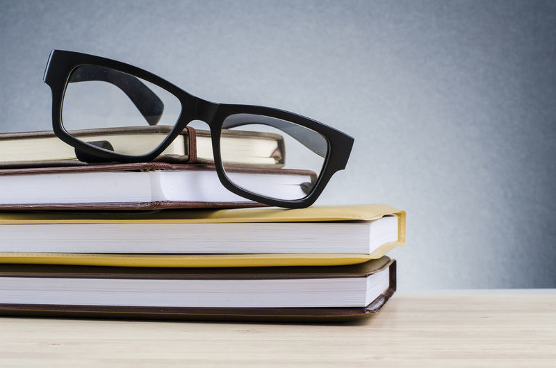 pectacles on stack of books over beautiful gradient background with reverberation Glasses Table Indoors  Eyeglasses  Publication Still Life Book Education No People Close-up Stack Eyesight Focus On Foreground Wood - Material Reading Glasses Wisdom Wood Furniture Absence Glass - Material Personal Accessory Eyewear