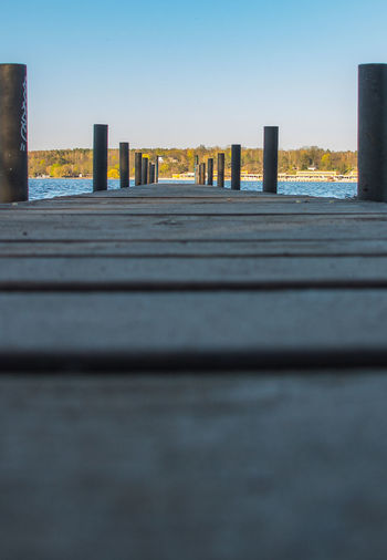 Surface level of wooden posts against clear sky