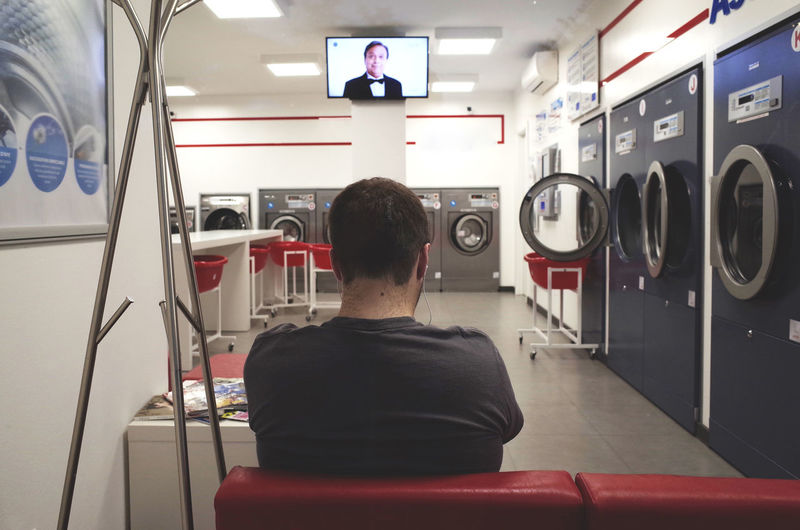 laundry sunday Casual Clothing City Life Everyday Lives Interior Views Laundry Leisure Activity Lifestyles Person Rear View Traveling Tv Urban Lifestyle Waist Up Waiting Washing Washing Clothes Washing Machine Watching Tv Window Dramatic Angles