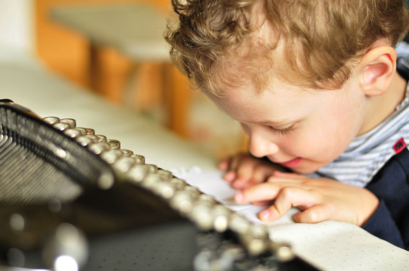 Close-up of boy with typewriter at table